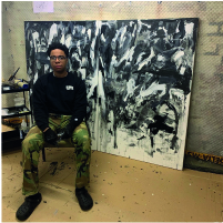 Portrait of Khari Worrell sat in front of large abstract painting.